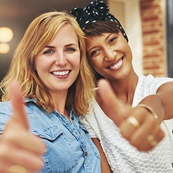 Two smiling women giving thumbs up