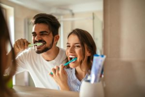 Couple brushing their teeth to avoid seeing an emergency dentist in Pearland